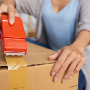 Woman using a tape dispenser to close a box
